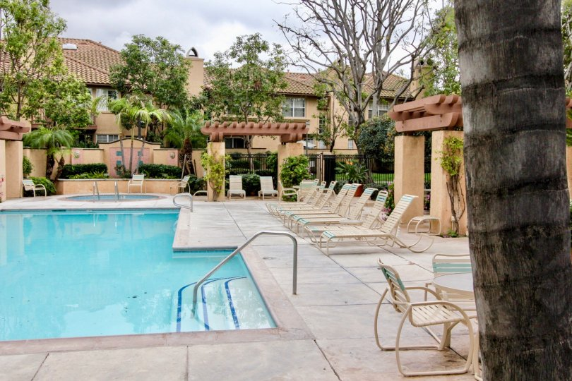 Pool area in Arcada Community in Tustin, California with hot tub and lounge chairs and tables.
