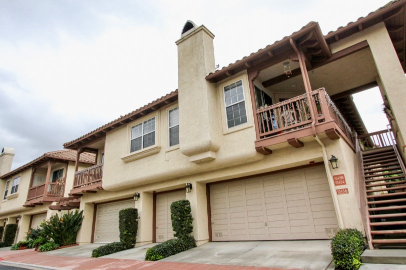 Street view of residences in Arcada in Tustin, California. Stairways adorn the units and attached garages are included.
