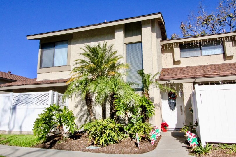 Beautiful home on a bright day with a blue sky in the community of Briarcliff Village in Tustin, California with palm trees!