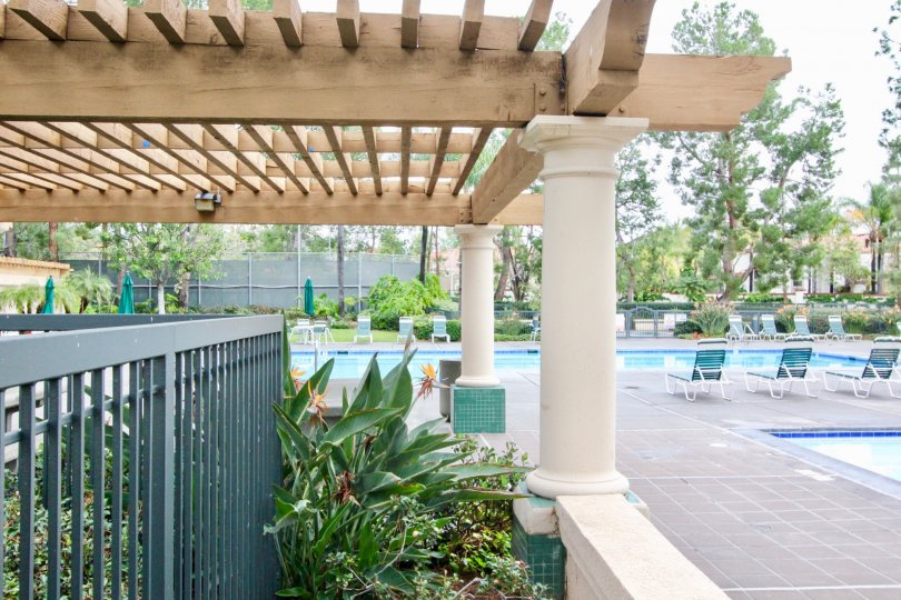 The swimming pool area, complete with chairs and a lovely pergola in the community of Corte Villa in Tustin, California