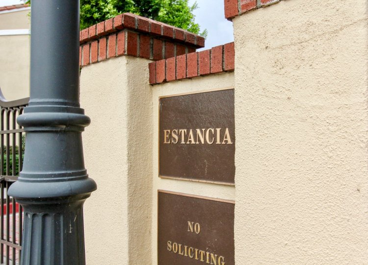 A sunny day in the area of Estancia, outside, brick, gate, welcome sign, trees