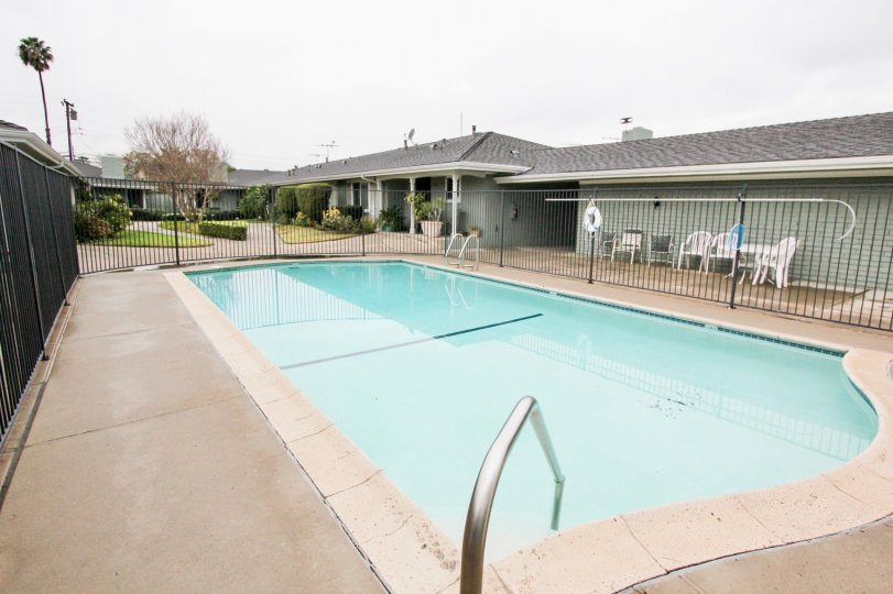 THIS Image represents the beautiful swimming pool which have the lot of chairs and views the longsite trees plants are there in the city of Tustin