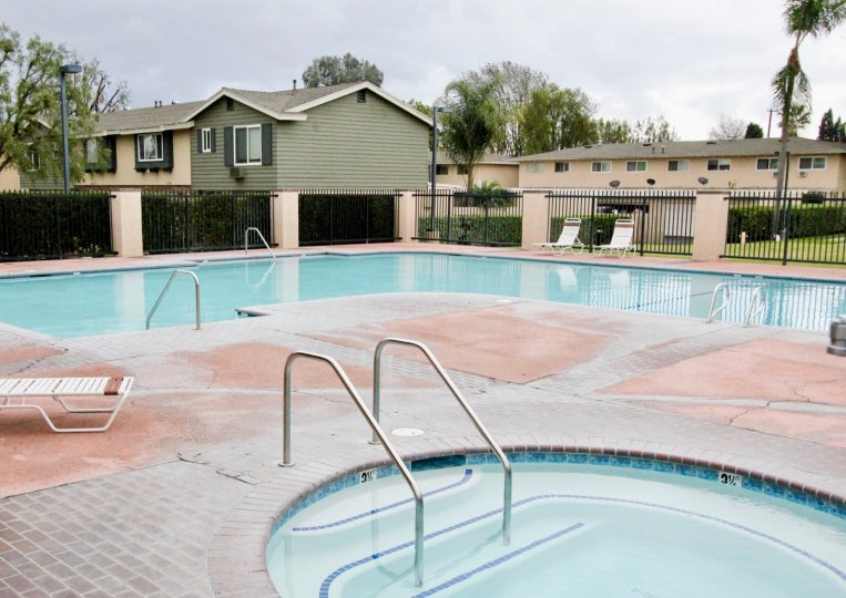 Resident's pool and hot tub in Influential Square in Tustin, California. Fenced pool area and lounge chairs around pool.