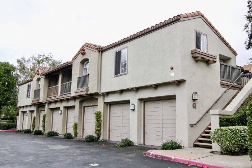 A sunny day at the Mandevilla community with stucco, spanish tile, upstairs patios, and private garage parking