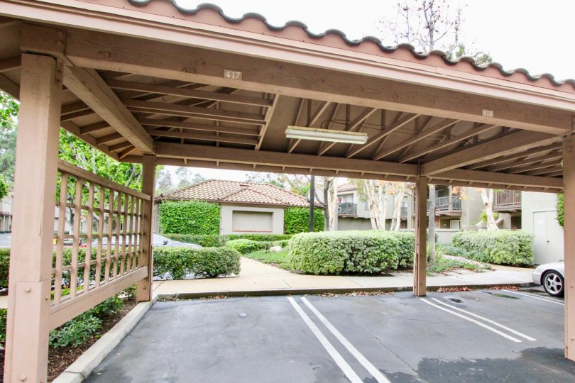 A sunny day in the area of Mandevilla, condo car port, vehicle, bushes, fence, sidewalk