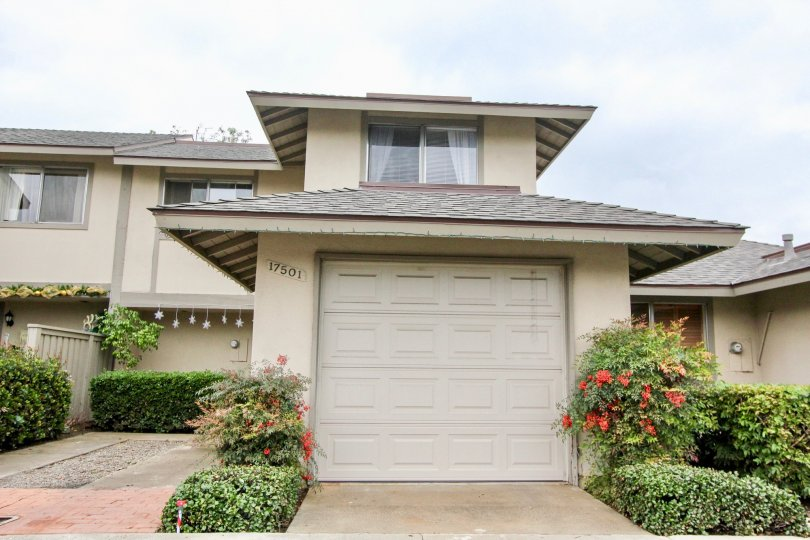 2 Storey attached home with single car garage and well maintained hedges and shingle roofs in Tustin