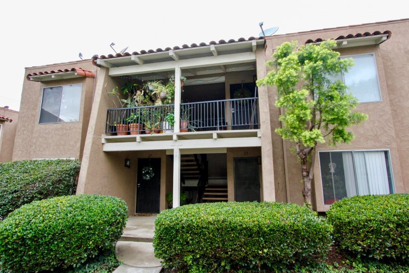 A simple two-storey townhouse with a covered balcony in the Rancho San Juan community.