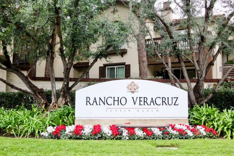 Large decorative community sign with professionally gardened flowers and mature trees in Rancho Veracruz