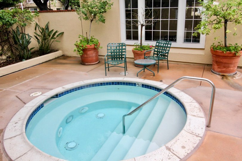 THIS IMAGE REPRESENTS THE SMALL SWIMMING POOL WHICH IS IN THE INSIDE THE HOUSE, THAT HAS NEARBY PLANTS AND CHAIRS IN THE CITY OF TUSTIN