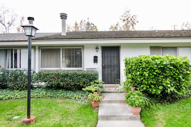 A great home in Sycamore Garden with tons of bushes in front.