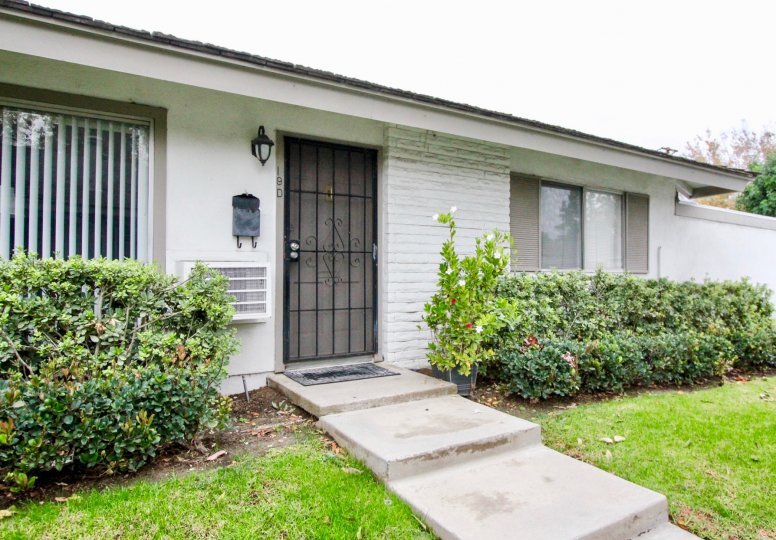 A simple bungalow with gated front doors and white walls in the Sycamore Gardens community.