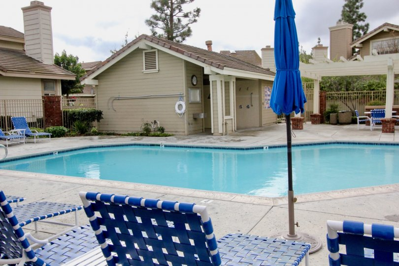 Moderate sized pool with adjacent deckspace and change room building and blue themed patio chairs in Sycamore Glen