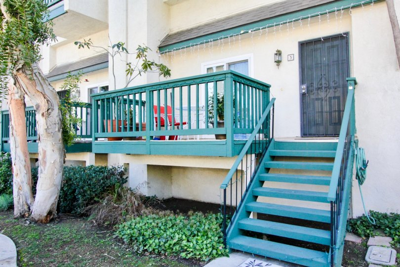 Wooden stairs and fence on a town home have been painted teal in the Tustin Commons