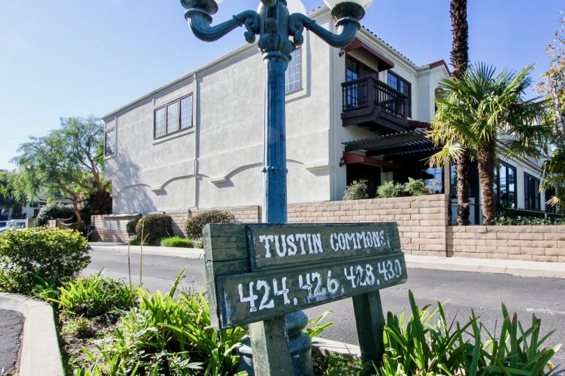 A sunny day by the Tustin Commons sign in front of a light pole with trees and houses behind the light pole