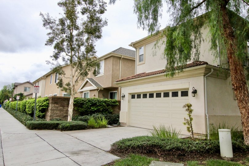 A sunny day at Tustin Field with two garage parking, green landscaping and tall trees