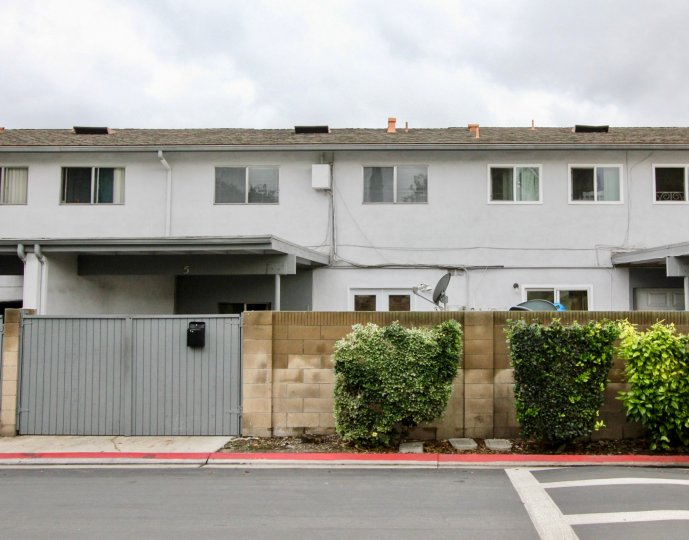 Two-storey townhouses with plain white walls and sliding windows in the Tustin Imperial community.