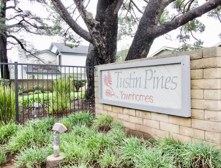 Tustin Pines Townhomes entrance sign on tan bright with mature trees, tall fencing and community landscaping