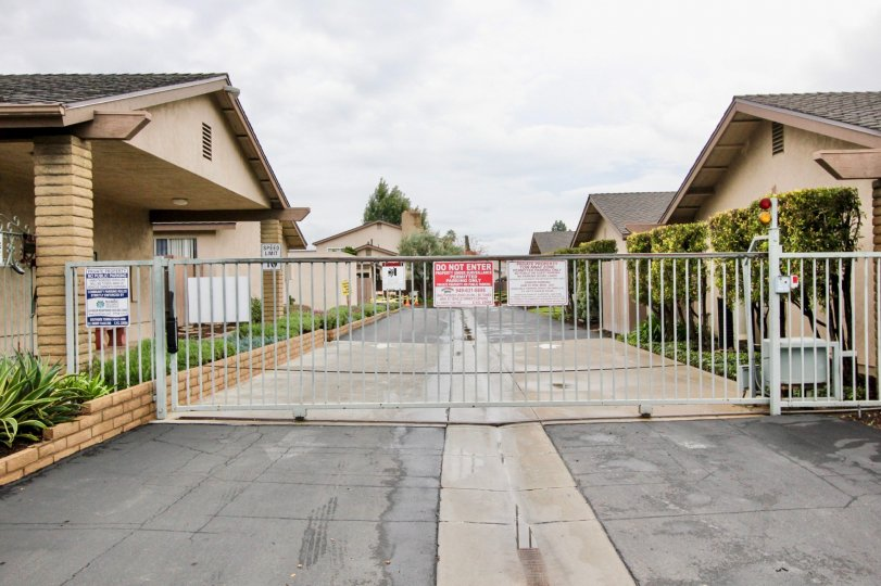 A sunny day at the private gated entrance to Tustin Verdes community with tall automatic gate
