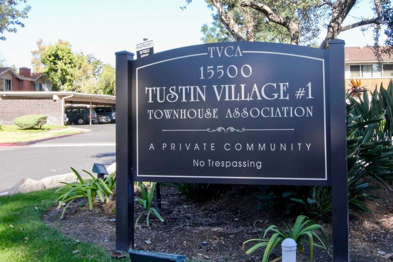 THE FLATS IN THE TUSTIN VILLAGE WITH THE ADDRESS BOARD, PLANTS, TREES, CAR PARKING