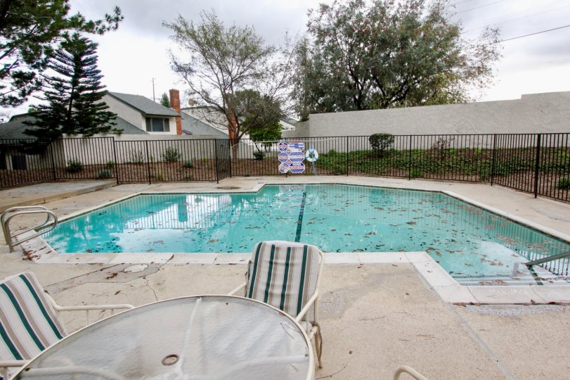 A pool area with leaves fallen into it in the Charter Hill community