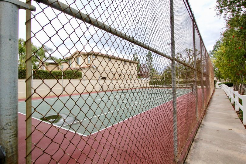 Tennis court surrounded by a metal fence in the community of Jamestowne Homes.