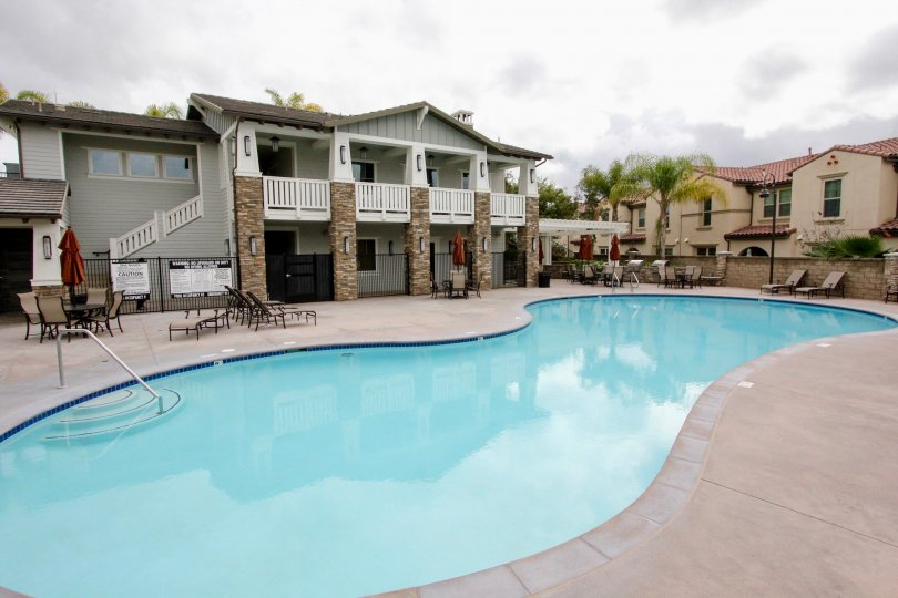 A pool in the Community: Palisades at Vista Del Verde with deck chairs and a stone fence.