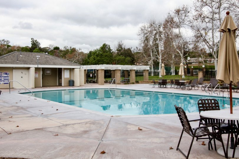 A pool in the Rancho Dominguez Townhomes with deck chairs and tables on a cloudy day.