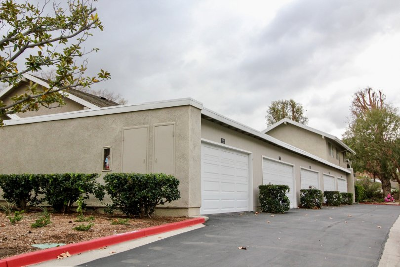 The road in Rancho Dominguez Townhomes has few villa's with car shed and bushes with trees