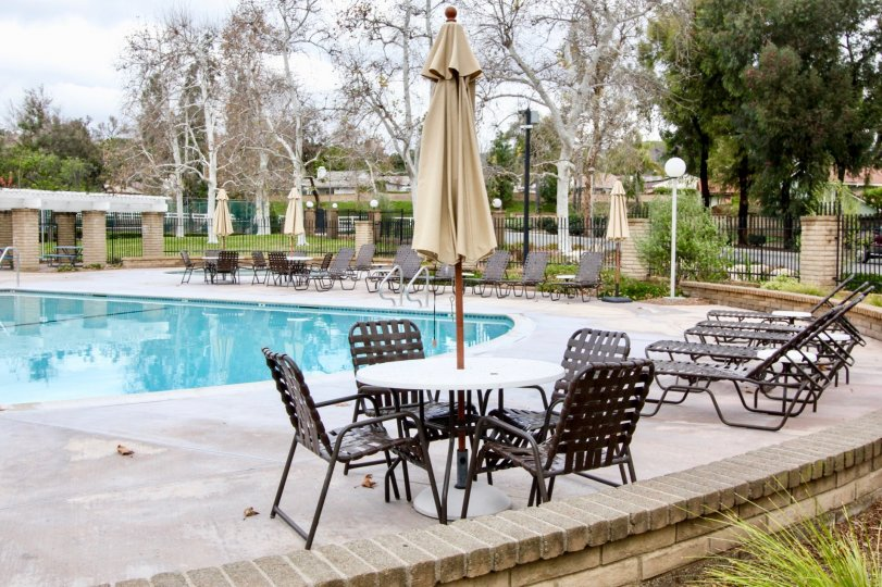 The sunny day in the Rancho Dominguez Townhomes with swimming pool and chairs.