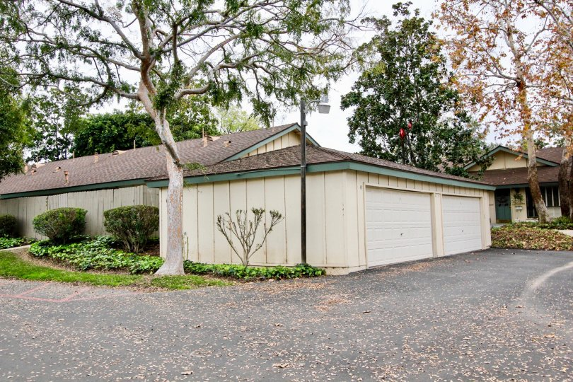 A shorter level garage with 2 doors and lots of green trees located in Rancho Linda community.