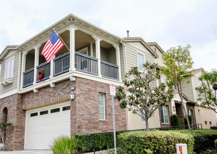 A corner bunglow with an American flag hanging on the balcony railings in San Lorenzo community