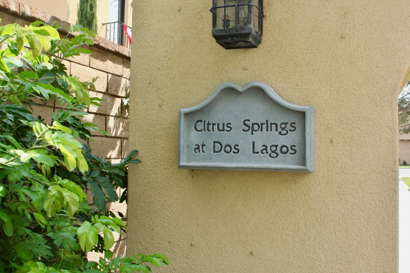 A decorative sign sits on a wall under a lamp at the Citrus Springs community.