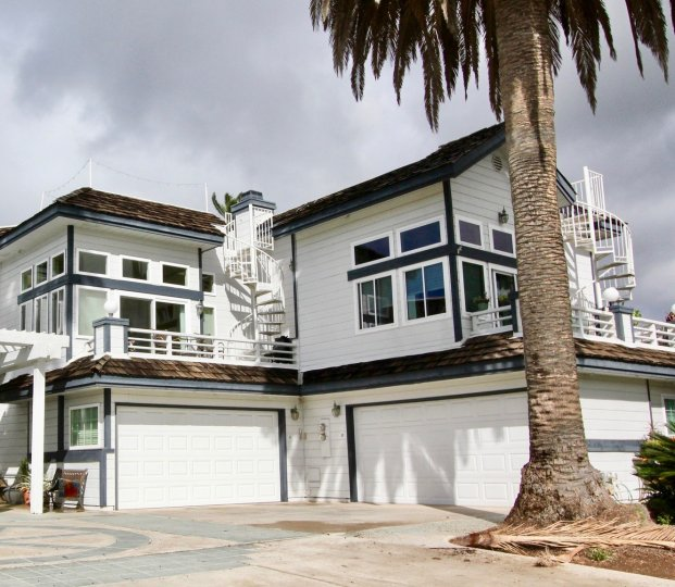 Large white and black house with a palm tree at 302 Hemlock on a cloudy day.
