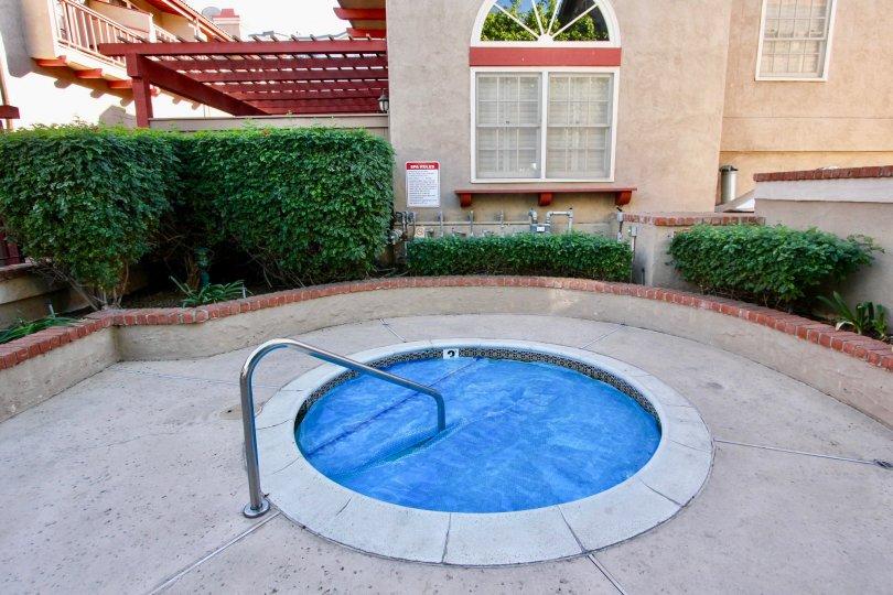 A crystal blue hot tub with metal railing inside Fairways South in Carlsbad CA