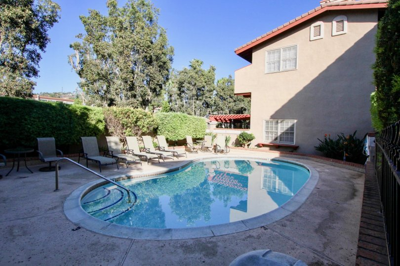 community pool with chairs next to a home in Carlsbad California