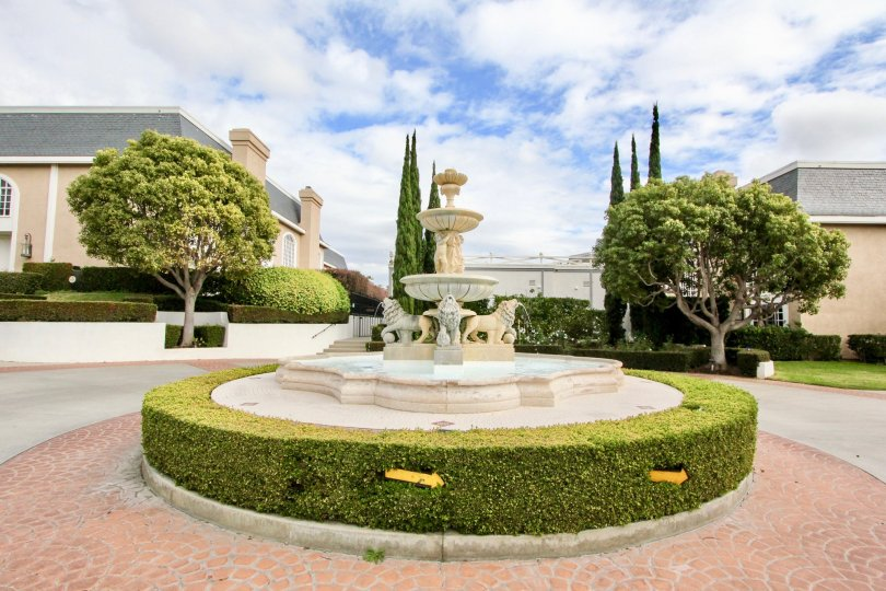 Breathtaking fountain carved stone centerpiece with perimeter hedges and a brick inlay road at the Jockey Club