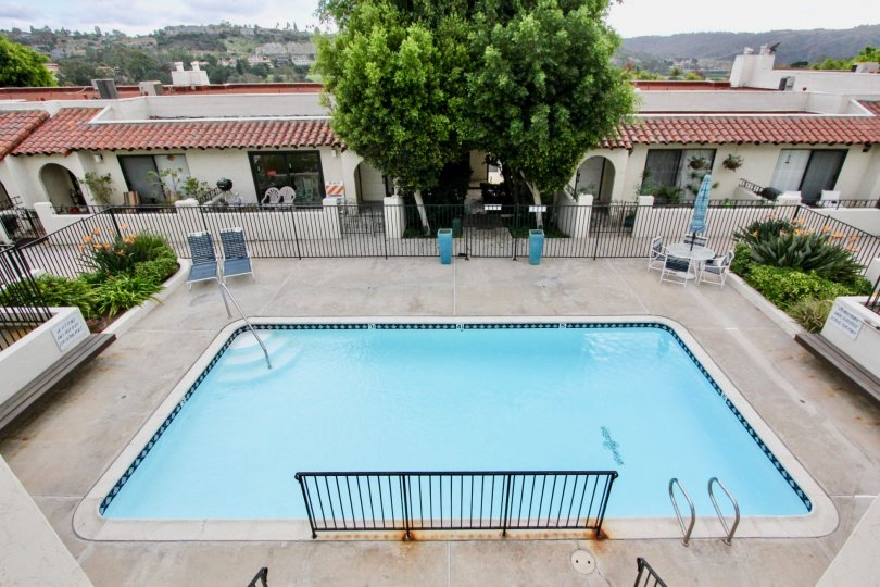 Top view of blue pool, chair & trees in La Costa Pacific Villas, Carlsbad, CA