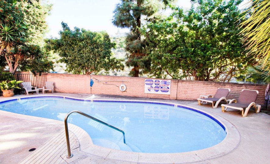 A pool's safety rules and some lounge chairs sit in front of a small pool in the La Costa South community of Carlsbad, California.