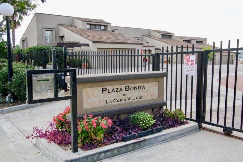 THE APARTMENT IN THE LA COSTA VILLAGE WITH THE NO PARKING BOARD, PLAZA BONITA BOARD, METER BOX, PLANTS, TREES