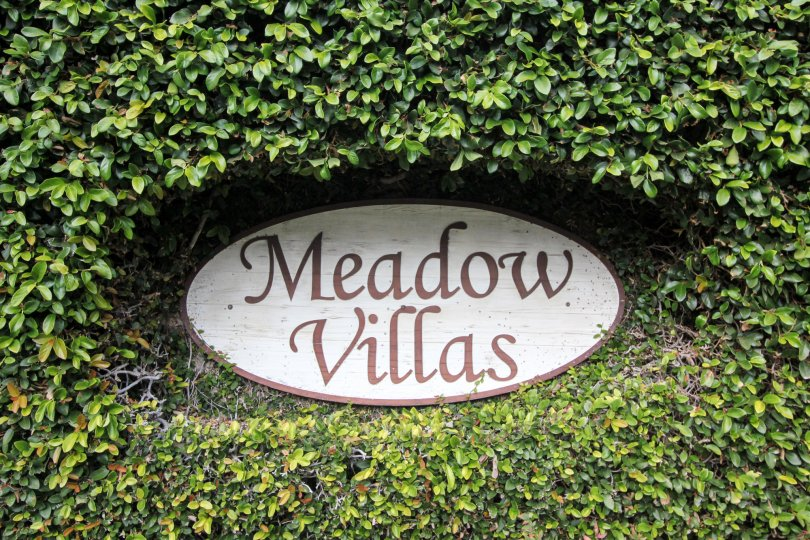 "An oval sign with the words ""Meadow Villas"" surrounded by plants"