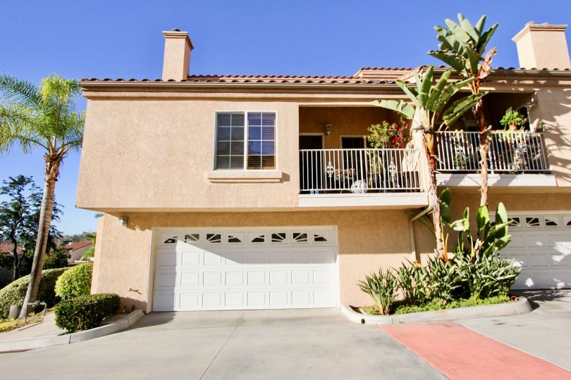 A spacious two story brown condominium building with a white garage door in Meadowview Townhomes in Carlsbad CA