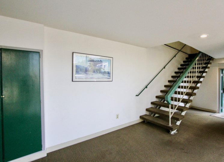Lower level of home. White walls, brown carpet, green door and staircase rails.