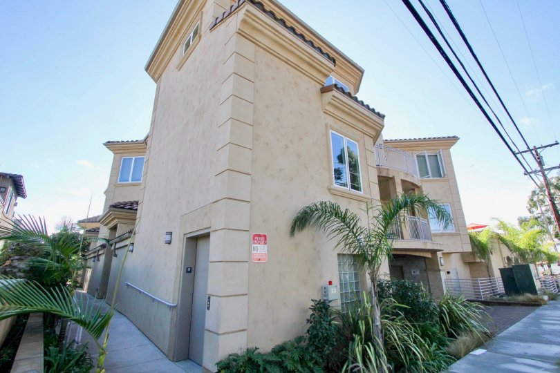 A two story brown building lined with assorted palms located in Villagio in Carlsbad CA