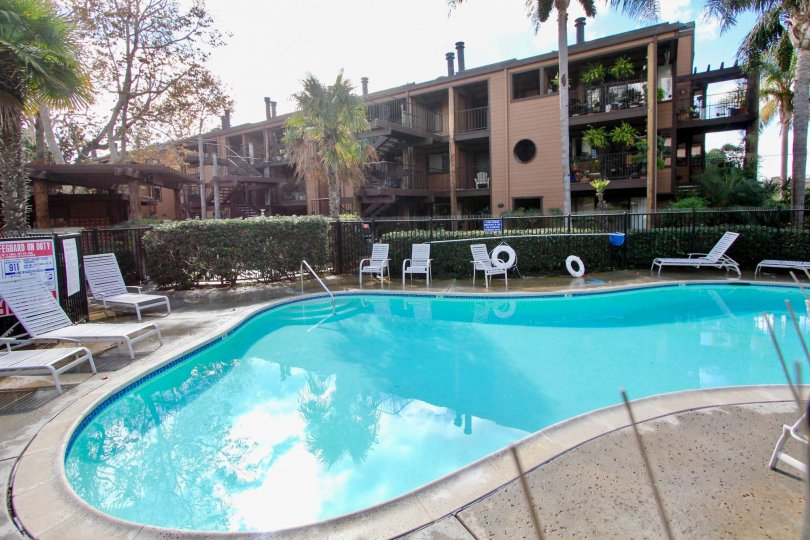 Inside the Apartment in Windsong Palms has swimming pool and chairs with sign board attached in gate