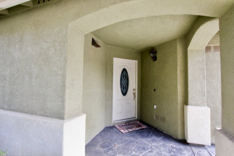 A white door with a glass oval center located in Chula Vista CA at Ada Terrace