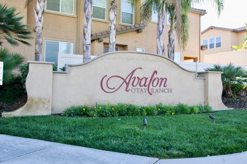 The name of the Avalon condos rests on a sign in a lawn in front of a condo building