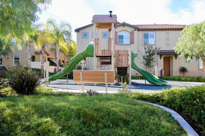 Green wavy slides protrude from a jungle gym at Avalon condos