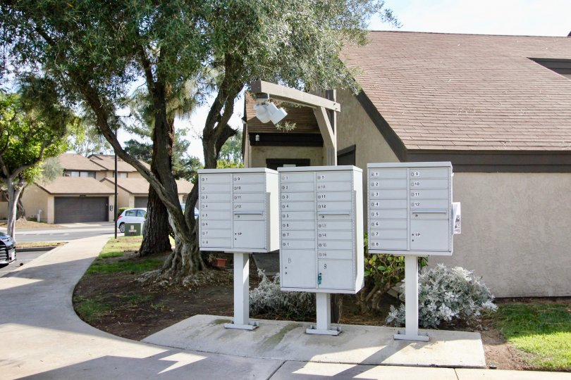Curbside located community mailboxes with large trees and shrubs at Bonita Terrace