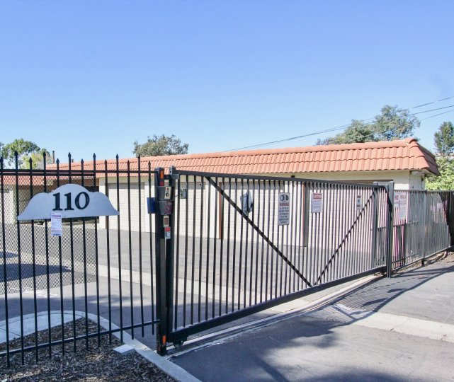 THE 110 BUILDING IN THE BRENTWOOD ARMS WITH THE STEEL GATE, ROAD SIDE, POST WIRES