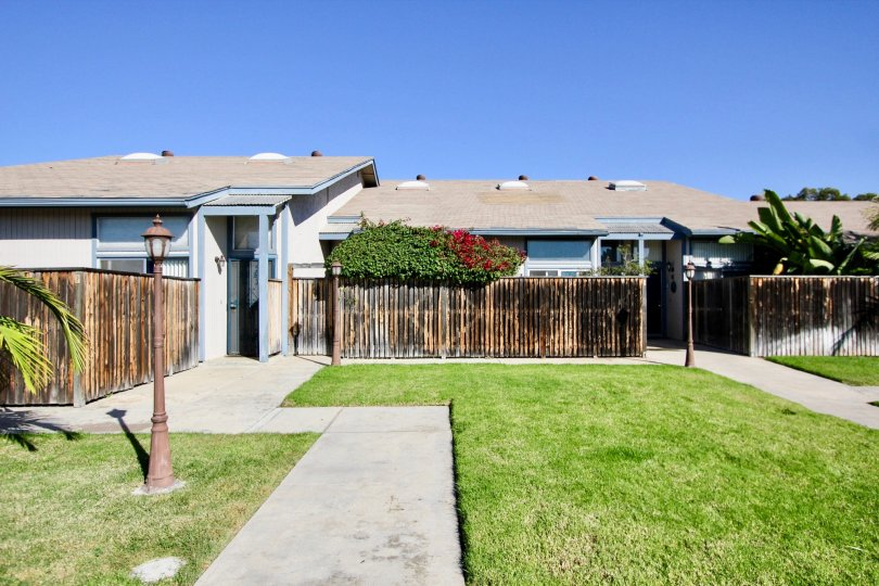 Large front lawn with high wooden privacy fence for attached homes at Casa Vianney